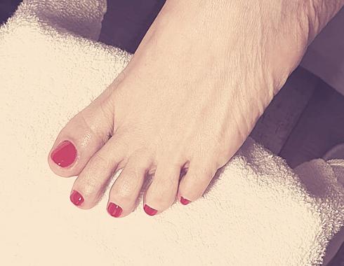 Női pedikűrözött lábfej élénkvörös géllakkal